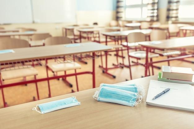 학교 교실에서 교사와 학교 책상에 얼굴 마스크.