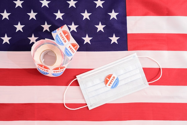 Face mask of a proud voter during the democratic elections in the usa with stickers on the patriotic american flag.