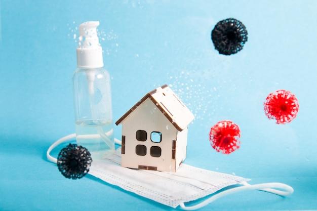 파란색 배경에 얼굴 마스크 작은 집과 바이러스 모델