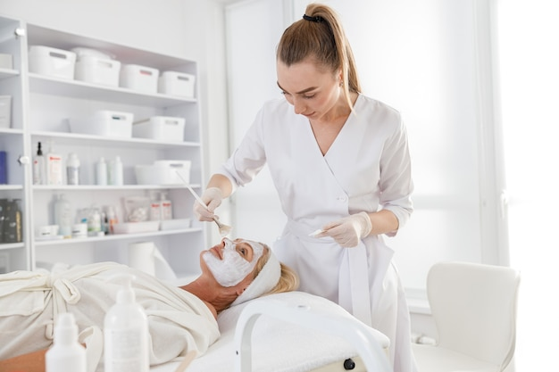 フェイスマスク、スパビューティートリートメント、スキンケア。スパサロンで美容師による顔のケアを受けている年配の女性、側面図。