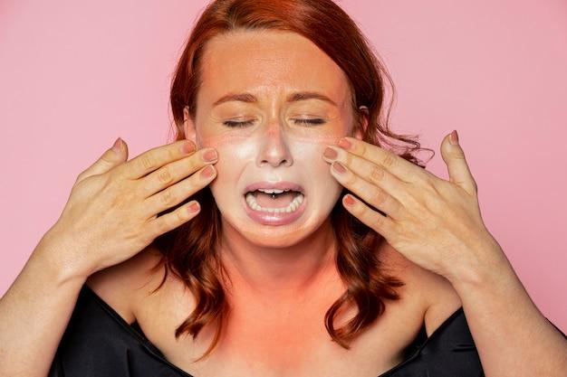Maschera per il viso linea di abbronzatura sul viso di una donna sconvolta