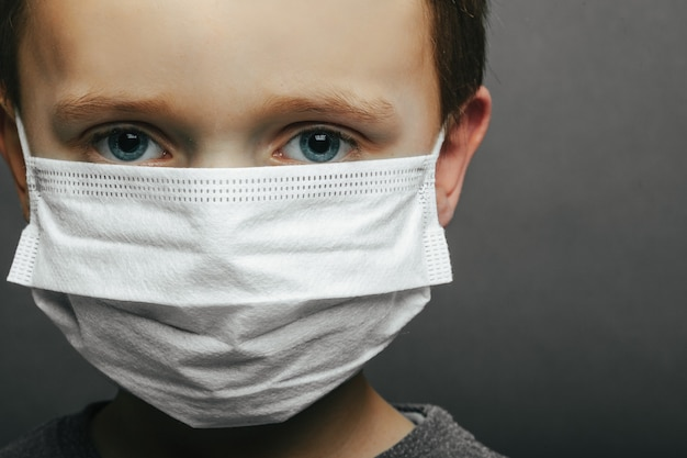 Face of a mask-wearing boy with fear in the eye close-up on a gray surface. coronavirus and air pollution pm2.5 concept