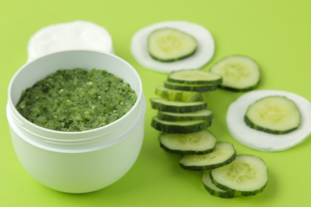 Face mask with cucumber. cosmetics with cucumber extract on a bright green background. spa. beauty.