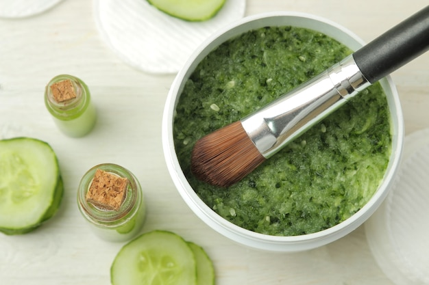 Face mask with cucumber. cosmetics with cucumber extract on a white wooden table. spa. beauty. top view