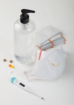 Маска для лица с дезинфицирующим гелем, спиртовые салфетки для рук на белом с термометром и таблетками. лучшая защита от коронавируса, микробов, бактерий и вирусов.