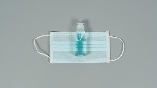 灰色の背景にフェイスマスクとアルコールジェル。 covid-19、およびその他の空中感染に対する保護。コピースペース