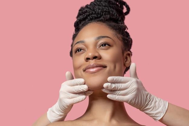 フェイスマッサージ。フェイスマッサージをして喜んでいるアフリカ系アメリカ人の女性