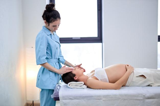 フェイスマッサージ。女性マッサージ師によるスパトリートメントを受けるアジアの穏やかな女性、側面図。妊娠中の中国人女性は、リラックスして休んでソファに横たわっています。自然の美しさ、妊娠、スパのコンセプト