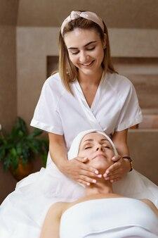 Массаж лица. крупным планом взрослая женщина, получающая спа-массаж в спа-салоне красоты. спа-уход за кожей и телом. косметические процедуры для лица. косметология.