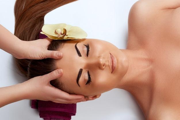 フェイスマッサージ。ビューティースパサロンでスパマッサージ治療を受けている若い女性のクローズアップ
