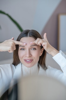 Face massage. cute young woman doing face massage in front of the mirror and looking relaxed
