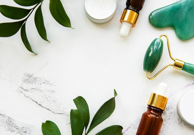 白い大理石の背景に化粧品とフェイスマッサージ翡翠ローラー