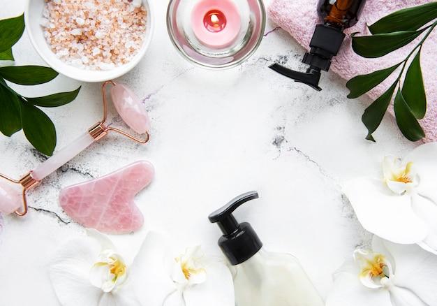 白い大理石のテーブルに化粧品とフェイスマッサージ翡翠ローラー