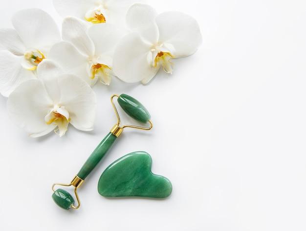 白い背景の上のマッサージ翡翠ローラーと蘭の花