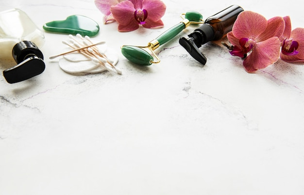 白い大理石の表面に翡翠ローラーと化粧品を使ったフェイスマッサージ
