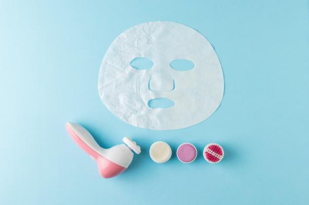 Массажер для лица с насадками и полуразглаженной маской на синем фоне. концепция омолаживающего воздействия на кожу.