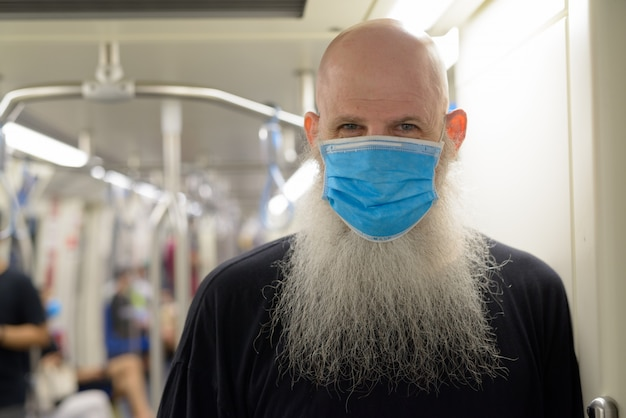 Face of mature bald bearded man with mask standing with distance inside the train