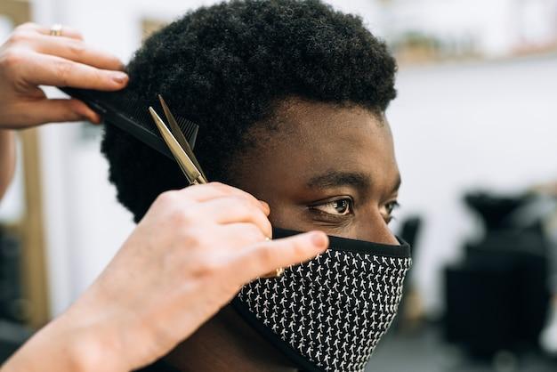 코로나 바이러스로 인해 얼굴에 검은 마스크가 달린 미용실에서 머리를 자르는 흑인 남자의 얼굴. 머리카락은 아프로 같다. 가위는 황금색입니다.