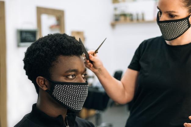 코로나 바이러스로 인해 얼굴에 검은 마스크가 달린 미용실에서 머리를 자르는 흑인 남자의 얼굴. 미용사는 또한 마스크를 착용합니다. 머리카락은 아프로처럼