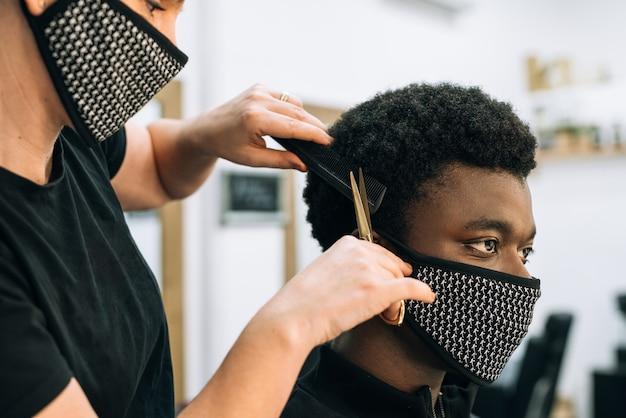 코로나 바이러스로 인해 얼굴에 검은 마스크가 달린 미용실에서 머리를 자르는 흑인 남자의 얼굴.