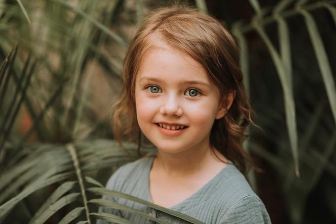 熱帯の葉に囲まれた少女の顔美しい赤ちゃんのクローズアップの肖像画