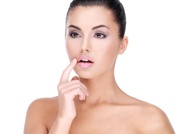 Лицо красивой молодой женщины с пальцем у губ - на белой стене