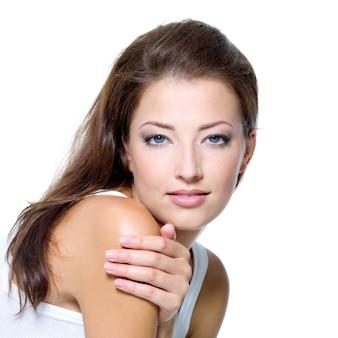白で隔離されるきれいな肌を持つセクシーな美しい若い女性の顔