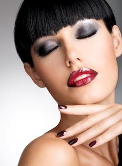 아름다운 어두운 손톱과 섹시한 붉은 입술을 가진 여자의 얼굴. 검은 머리를 가진 패션 모델
