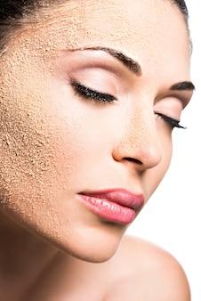피부에 화장품 파우더를 가진 여자의 얼굴-흰색에 고립