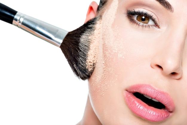 頬の皮膚にパウダーを塗った女性の顔