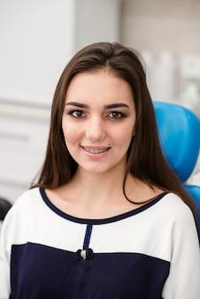 歯にブレースを付けた若い女性の顔。健康的な笑顔