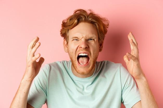 ピンクの背景の上に欲求不満に立って、怒りと怒りを凝視し、怒りと呪いを凝視し、憎しみと攻撃を表現し、叫び、握手する怒っている赤毛の男の顔。