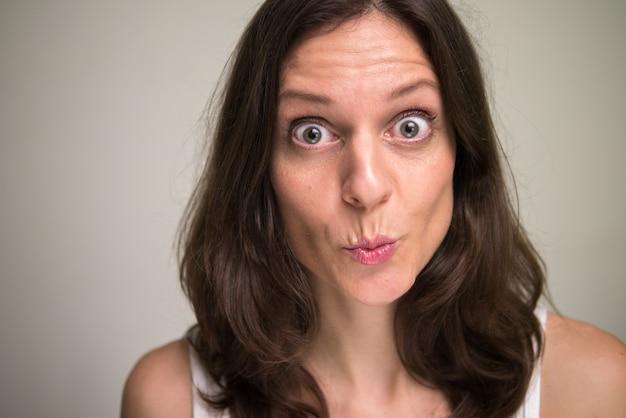 Лицо красивой женщины с каштановыми волосами выглядит шокированным