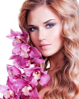 健康な肌と白い壁にピンクの花を持つ美しい女性の顔。