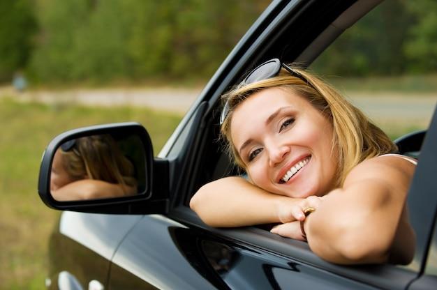新しい車の中で美しい若い幸せな女性の顔-屋外