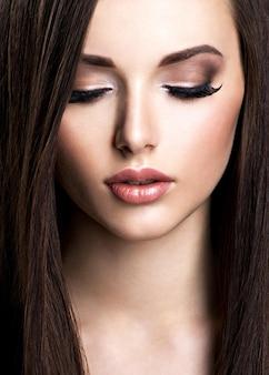 茶色のメイクとストレートヘアの美しい若い女性の顔