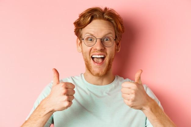 眼鏡とtシャツを着た幸せな赤毛の男の顔、親指を立てて興奮しているように見え、ピンクの背景の上に立って、クールなプロモーションを承認し、賞賛します。