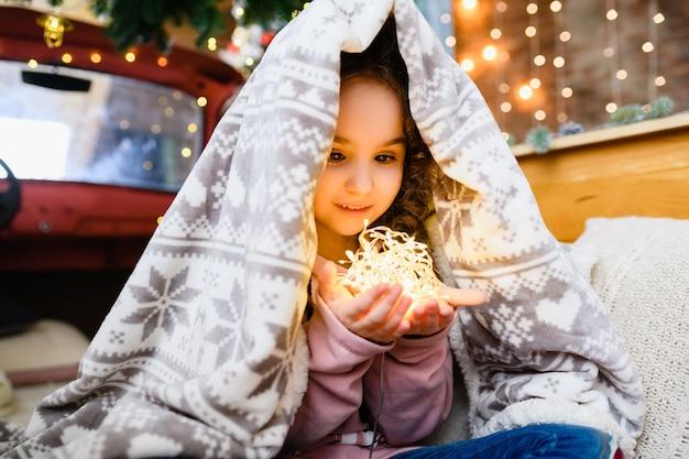 따뜻한 격자 무늬로 덮인 행복한 어린 소녀의 얼굴과 마법의 크리스마스와 새해 배경에서 led 화환 조명을 들고