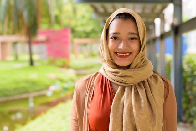 Лицо счастливой молодой красивой индийской мусульманской женщины, улыбаясь в парке