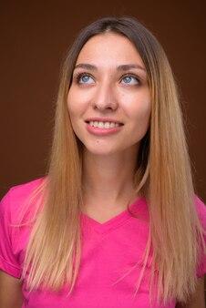 幸せな若い美しい女性の笑顔と思考の顔