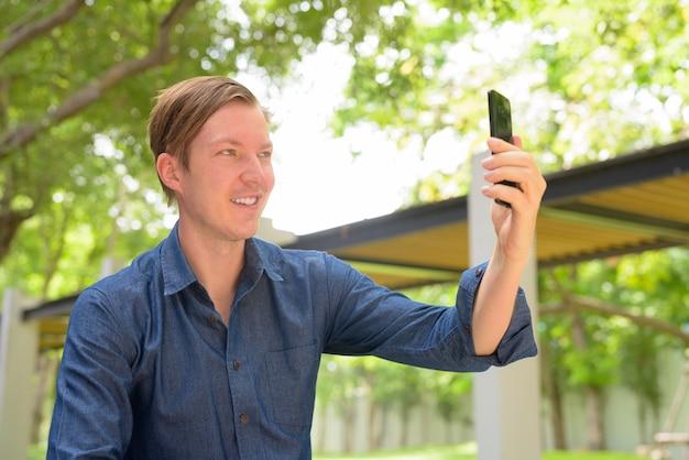 Лицо счастливого молодого красивого белокурого бизнесмена, делающего селфи в парке на открытом воздухе