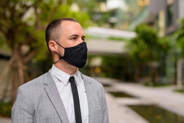 自然と街でマスクを考えて身に着けているヒスパニックのはげビジネスマンの顔