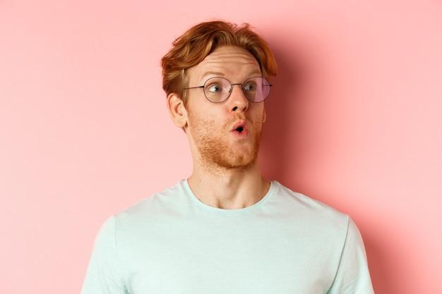 생강 머리와 수염을 가진 흥미 진진한 젊은 남자의 얼굴은 눈썹을 올리고 분홍색 배경 위에 서있는 오른쪽 상단 모서리 로고를보고 있습니다.