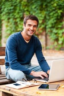 Лицо удовлетворения от работы. улыбающийся молодой человек работает на ноутбуке и смотрит в камеру, сидя за деревянным столом на открытом воздухе