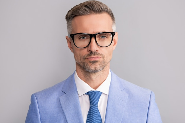 회색 배경에 우아한 재킷과 안경을 쓴 성숙한 사업가의 얼굴, 사업가.