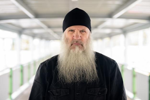 Лицо зрелого красивого бородатого мужчины на пешеходном мосту в городе