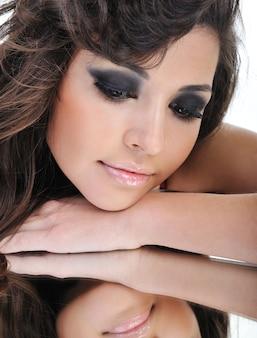 鏡を見て夢を見ているきれいな女性の顔