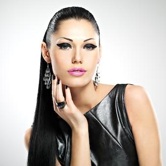 目の魅力的なファッションメイクと光沢のある髪型を持つ美しいセクシーな女性の顔。スタジオで白人の大人の女の子の肖像画