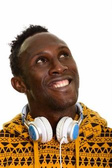 ヘッドフォンを浮かべて思慮深い若い幸せなアフリカ人の顔