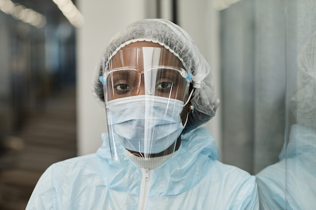 코로나바이러스로부터 보호하는 ppe 정장 의료 마스크와 안면 보호구를 쓴 피곤한 흑인 의료 간호사의 얼굴